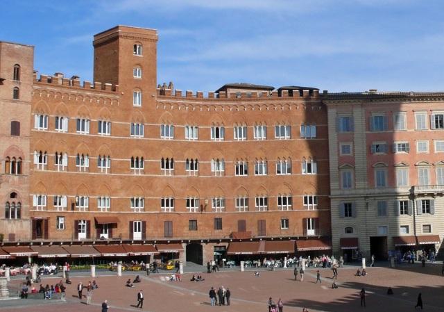Siena w Toskanii – przykład pozytywny: ujednolicona kolorystyka fasad i reklam (te są umieszczone na markizach, sprawia że przestrzeń staje się przyjazna ludziom, którzy chętnie spędzają tu czas. Fot. Krzysztof Worobiec.