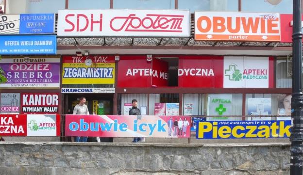 Nidzica – przykład negatywny: chaos kolorystyki i reklam, główny plac miasta zamieniony na parking – przestrzeń mało przyjazna ludziom. Fot. Danuta Worobiec.