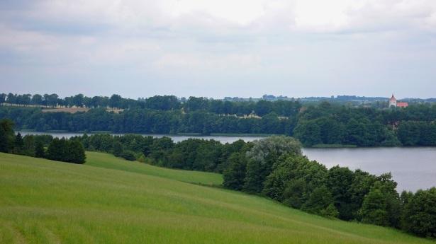 Harmonijny krajobraz – wzgórza morenowe, rynnowe jezioro Juno, dalej aleja przydrożna w tle gotycki kościół w Szestnie. Fot. K. Worobiec