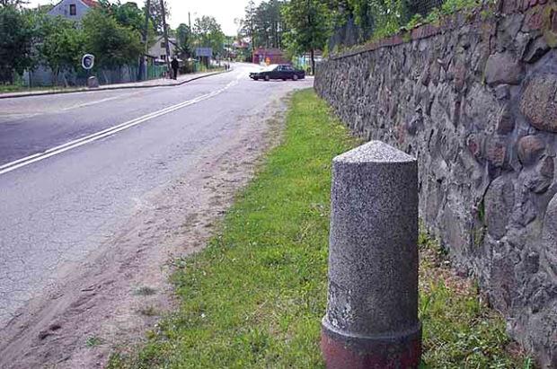 Kamień milowy we wsi Lutry, gm. Kolno. W głębi po lewej, obok budki telefonicznej, widoczny inny rodzaj kamienia przydrożnego. (Fot. A. Płoski)